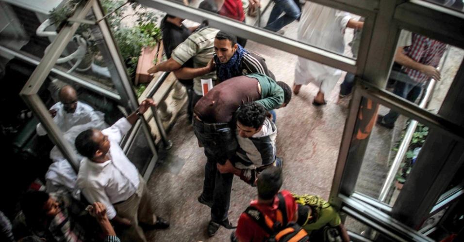 6.out.2013 - Homem carrega manifestante pró-Mursi ferido durante confronto com a polícia nas ruas de Gizé, cidade próxima ao Cairo, no Egito