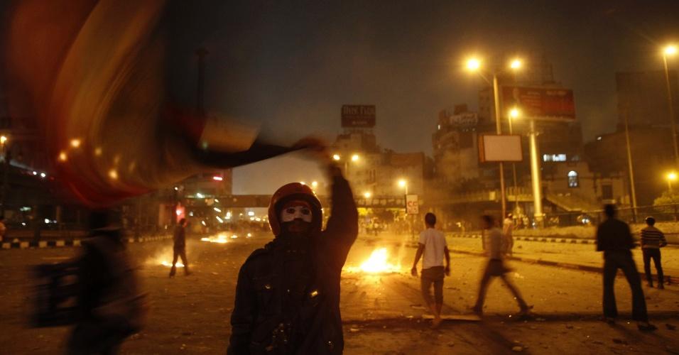 6.out.2013 - Manifestante estende bandeira egípcia durante confronto com membros da Irmandade Muçulmana que apoiam o líder deposto Mohamed Mursi em rua próxima à praça Ramsis, no Cairo, que leva à famosa praça Tahrir. Os confrontos entre partidários, opositores e forças de segurança deixaram ao menos 38 pessoas mortas no dia em que o país comemora o 40º aniversário da guerra árabe-israelense de 1973