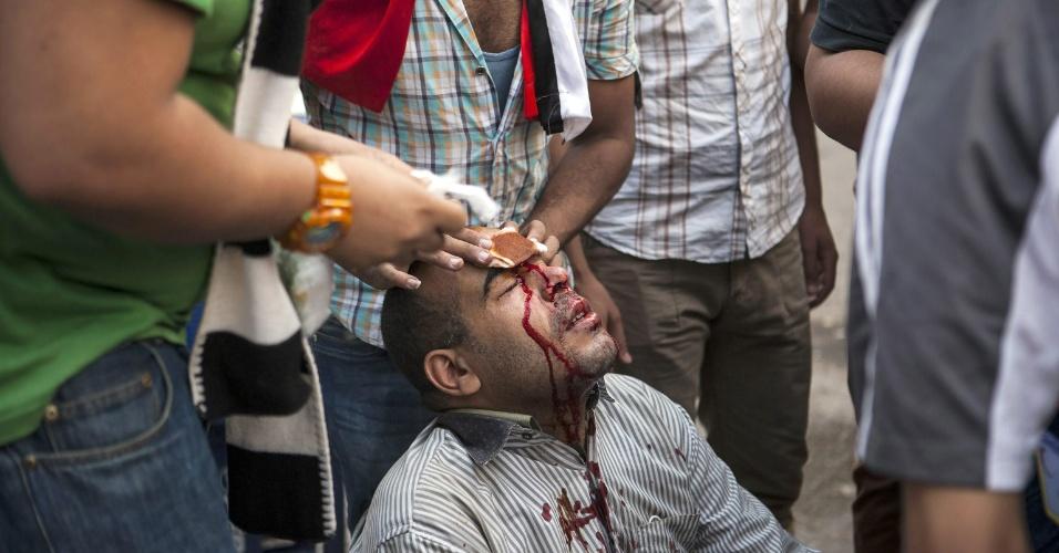 6.out.2013 - Manifestante pró-Mursi ferido recebe ajuda de colegas após confronto com a polícia nas ruas de Gizé, cidade próxima ao Cairo, no Egito