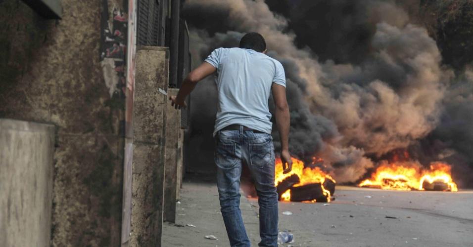 6.out.2013 - Simpatizante de Mohammed Morsi, presidente deposto do Egito, se protege de ataque atrás de um muro nas ruas de Gizé, cidade próxima ao Cairo. Confrontos entre partidários, opositores e forças de segurança deixaram ao menos 38 pessoas mortas no dia em que o país comemora o 40º aniversário da guerra árabe-israelense de 1973