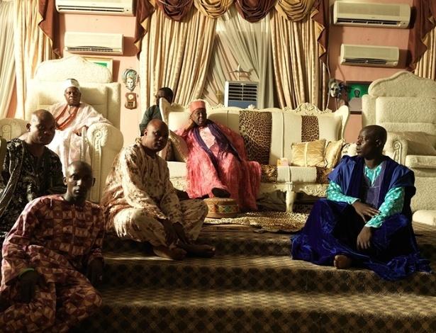 Rodeado por aparelhos de ar-condicionado e por sua corte, sua majestade imperial Oba Okunade Sijuwade, ou simplesmente Olubuse 2º, posa em seu trono. Ele é o monarca da tribo nigeriana de Ife