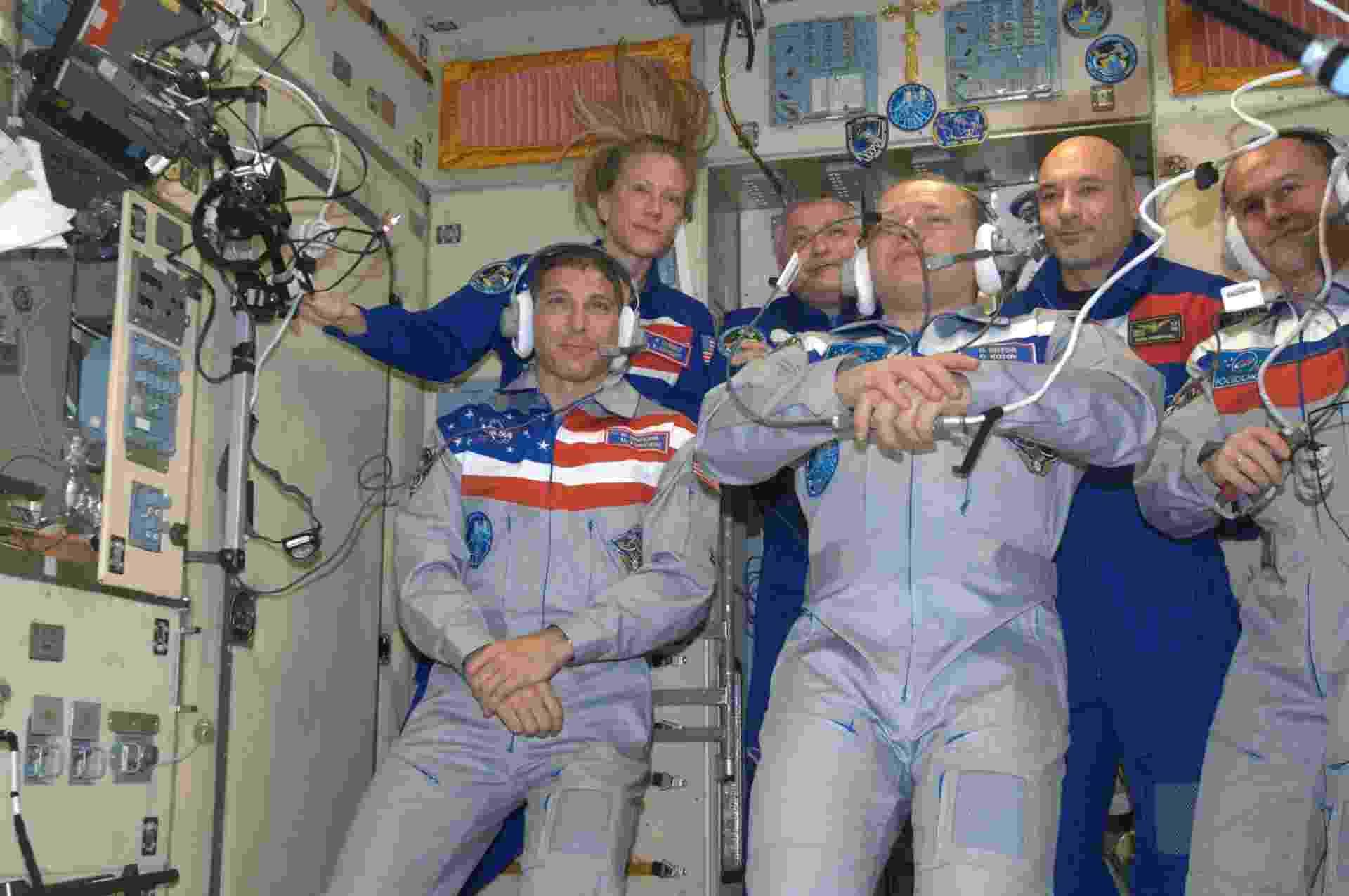 26.set.2013 - Mike Hopkins, Oleg Kotov e Sergey Ryazanskiy (à frente, da esquerda para a direita) conversam com parentes na Terra após chegada na Estação Espacial Internacional (ISS, na sigla em inglês). A nave russa Soyuz se acoplou à plataforma aproximadamente às 23h45 desta quarta-feira (25), no horário de Brasília - Volare Mission/ESA
