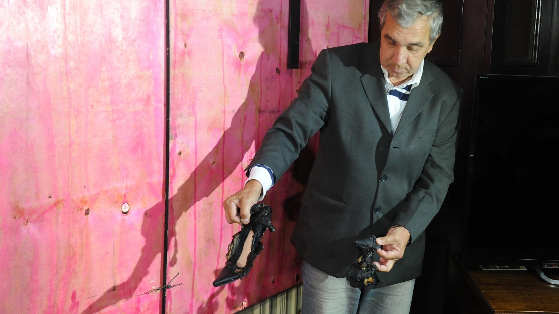 8.out.2013 - O coronel Ward Gusmão exibe um par de sapato feminino parcialmente queimado dentro da Câmara de Vereadores do Rio de Janeiro, nesta terça-feira (8), dia seguinte ao violento protesto de um grupo que se juntou ao grupo de professores
