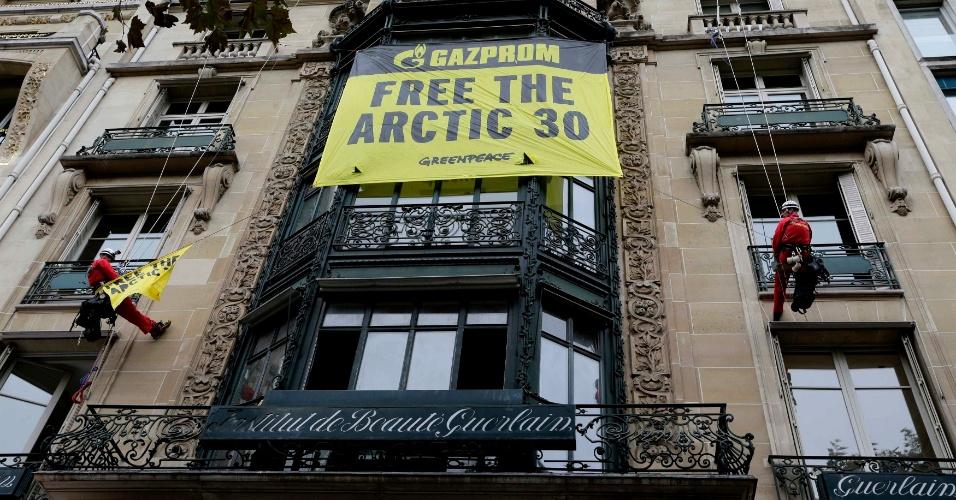 9.out.2013 - Ativistas do Greenpeace penduram cartaz na fachada da perfumaria francesa Guerlain, em frente à sede da petrolífera russa Gazprom em Paris. Além de posicionar contra a extração de petróleo no Ártico, a ação exige a liberação de 28 ativistas da organização, entre eles uma brasileira, acusada de pirataria depois de abordarem um navio petroleiro
