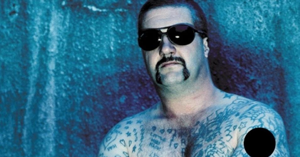 """9.out.2013 - Um dos criminosos mais perigosos da Austrália, Mark """"Chopper"""" Read, morreu nesta quarta-feira (9) em decorrência de um câncer no fígado. Na foto, ele posa para o cartaz de propaganda de uma marca de óculos de sol. Read, famoso pela quantidade de tatuagens e cicatrizes no dorso, admitiu ter matado 19 pessoas e passou 23 de seus 58 anos atrás das grades. Ele sempre matava e roubava de criminosos e traficantes, o que colaborou para sua popularidade na Austrália"""