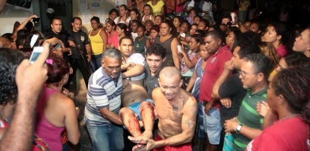 Familiares e amigos carregam detento ferido durante uma briga entre facções em São Luís