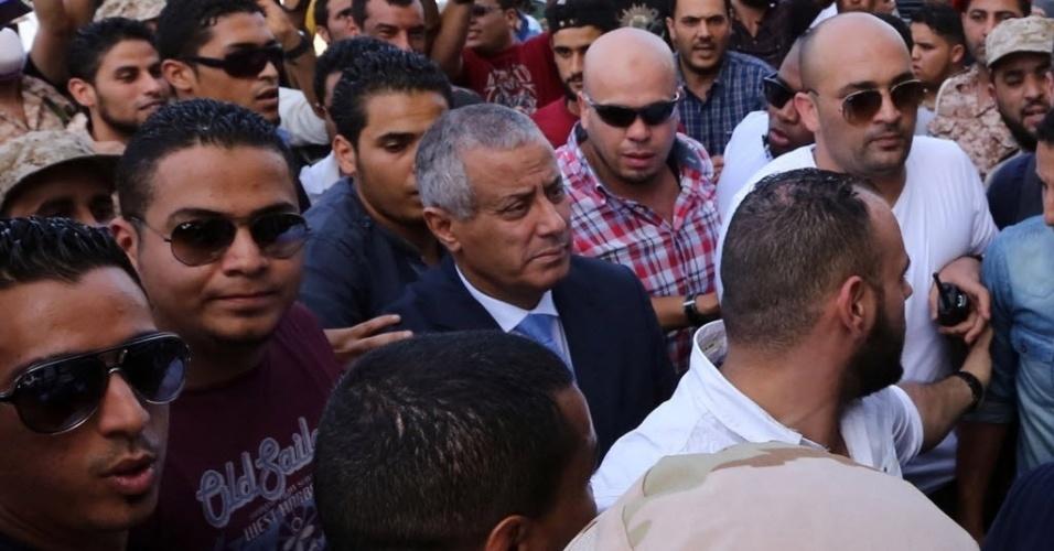 10.out.2013 - O primeiro-ministro líbio, Ali Zeidan (ao centro, de terno), chega à sede do governo em Trípoli, pouco depois de ter sido libertado do cativeiro de milicianos, nesta quinta-feira (10). Homens armados sequestraram Zeidan dentro de um hotel, onde reside, na capital da Líbia. Foram horas de negociação até a libertação