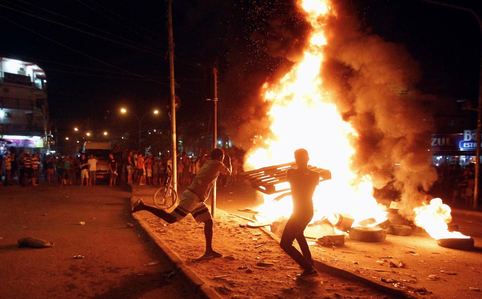 12.out.2013 - Manifestantes queimaram pneus, madeira e entulhos em confronto com policiais militares na estrada de Jacarepaguá, zona oeste do Rio