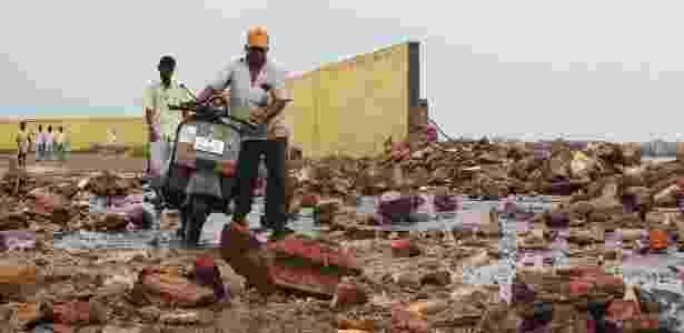 """Indianos caminham sobre escombros causados pelo ciclone """"Phailin"""" neste sábado (12) - Reuters"""