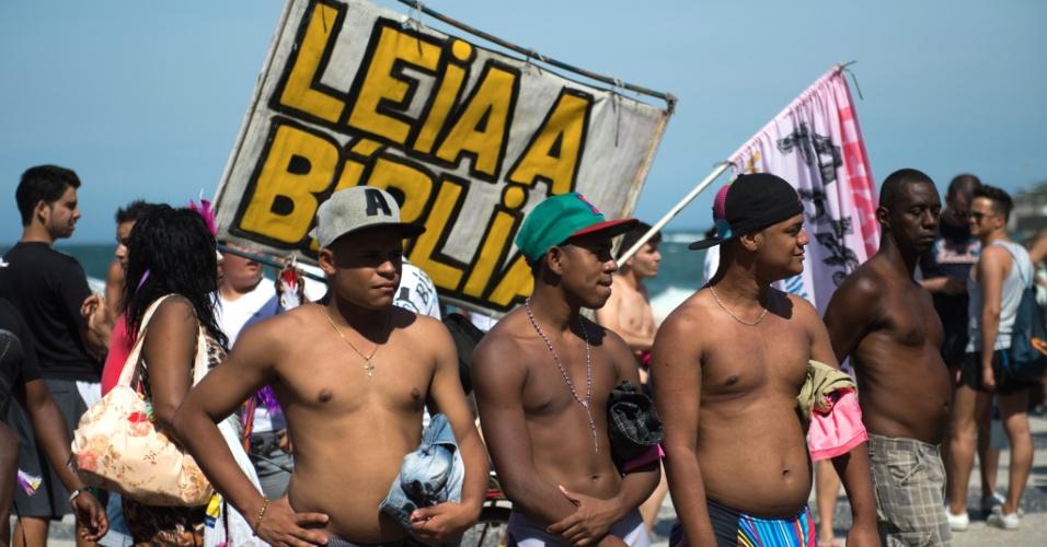 13.out.2013 - Homens observam a 18ª Parada do Orgulho Gay, na praia de Copacabana, zona sul do Rio de Janeiro, neste domingo (13), tendo atrás uma faixa onde se pode ler