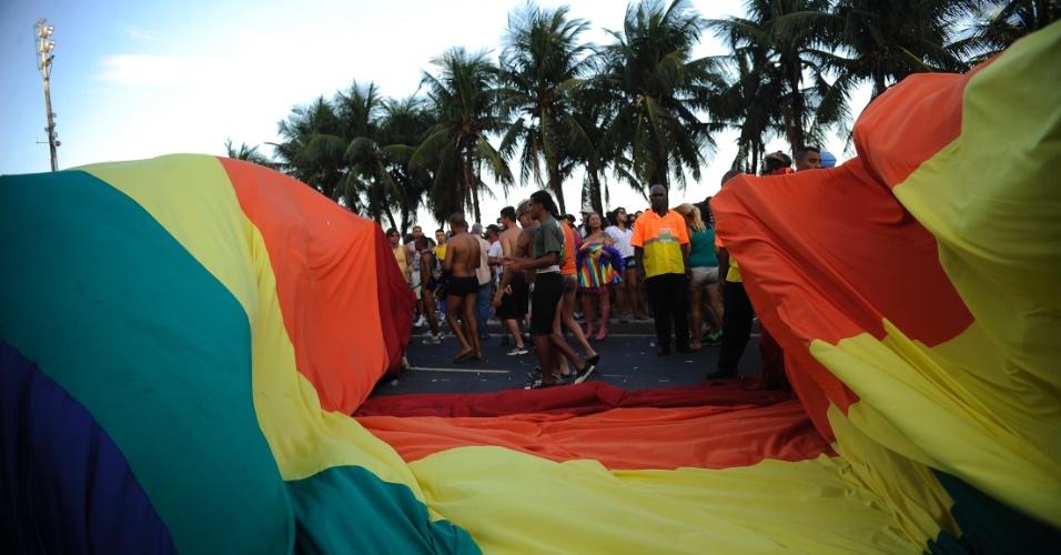 13.out.2013 - Pessoas carregam a bandeira símbolo do movimento LGBT durante a 18ª Parada do Orgulho Gay, na praia de Copacabana, zona sul do Rio de Janeiro, neste domingo (13)