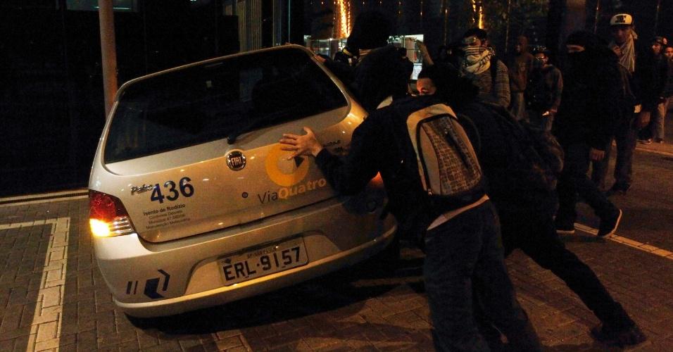 15.out.2013 - Black Blocs tentam derrubar um carro da ViaQuatro durante protesto contra a política educacional do governo de Geraldo Alckmin na capital paulista. A manifestação teve início no início da noite no largo da Batata, em Pinheiros. Manifestantes entraram em confronto com a polícia, que usou bombas de gás lacrimogêneo e efeito moral