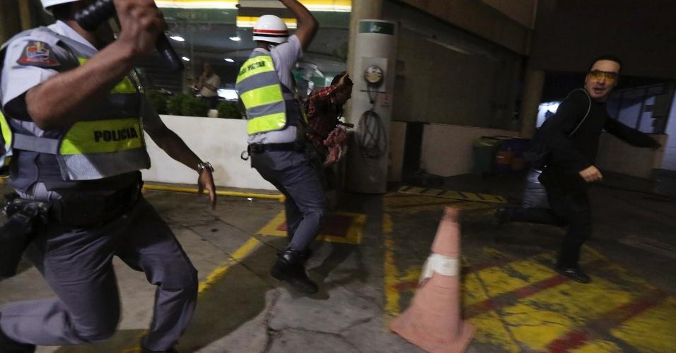 15.out.2013 - Cassetetes em mãos, policiais correm atrás de manifestante durante protesto contra a política educacional do governo de Geraldo Alckmin na capital paulista. A manifestação teve início no início da noite no largo da Batata, em Pinheiros. Manifestantes entraram em confronto com a polícia, que usou bombas de gás lacrimogêneo e efeito moral