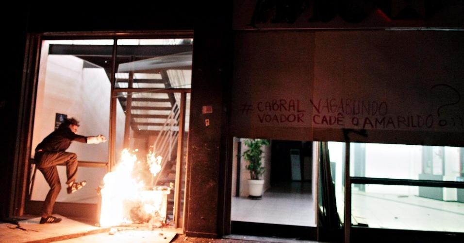 15.out.2013 - Manifestante coloca fogo em objetos na entrada de uma agência do HSBC após protesto de professores no centro do Rio de Janeiro na noite desta terça-feira (15)