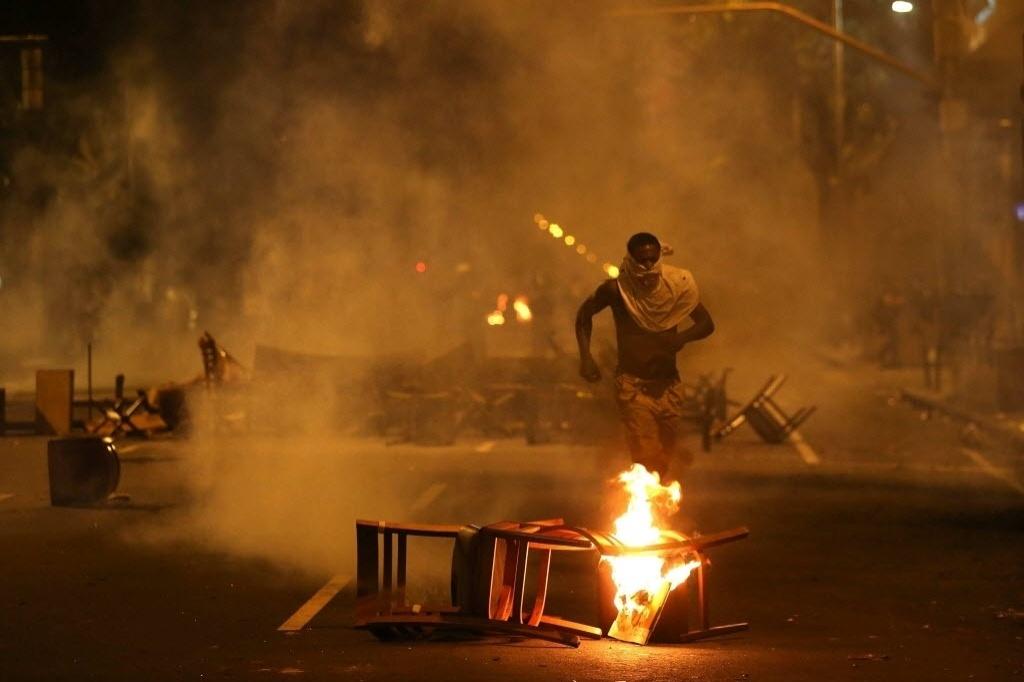 15.out.2013 - Manifestantes entram em confronto com a polícia após protesto de professores no centro do Rio de Janeiro na noite desta terça-feira (15)