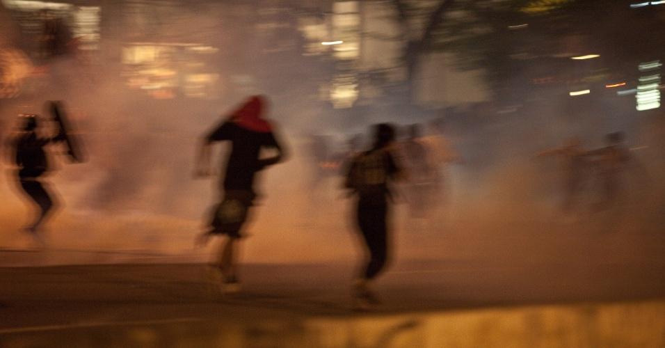 15.out.2013 - Manifestantes fogem da fumaça das bombas de gás lacrimogêneo e efeito moral lançadas pela polícia militar durante protesto contra a política educacional do governo de Geraldo Alckmin na marginal Pinheiros, sentido Interlagos, nesta terça-feira (15). A manifestação teve início no início da noite no largo da Batata, em Pinheiros