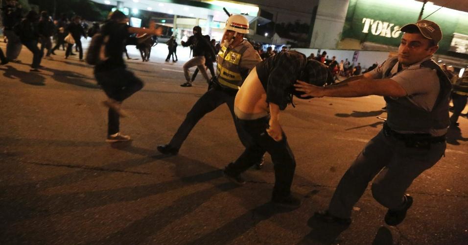 15.out.2013 - Policiais detêm manifestantes durante protesto contra a política educacional do governo de Geraldo Alckmin na zona oeste da capital paulista. A manifestação teve início no início da noite no largo da Batata, em Pinheiros. Manifestantes entraram em confronto com a polícia, que usou bombas de gás lacrimogêneo e efeito moral