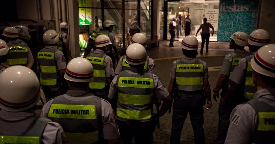 15.out.2013 - Policiais militares se posicionam em frente a estabelecimento comercial durante protesto contra a política educacional do governo de Geraldo Alckmin, que seguiu pela marginal Pinheiros, sentido Interlagos, nesta terça-feira (15). A manifestação teve início no início da noite no largo da Batata, em Pinheiros. Manifestantes entraram em confronto com a polícia, que usou bombas de gás lacrimogêneo e efeito moral