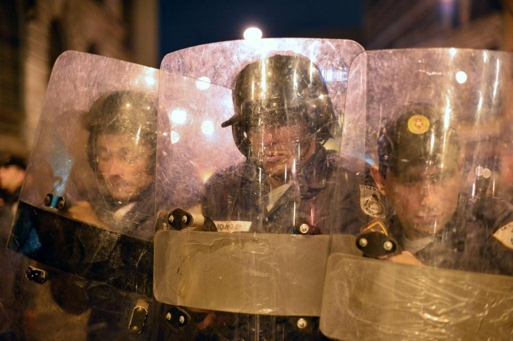 15.out.2013 - Policiais usam escudos para enfrentar manifestantes após protesto de professores no centro do Rio de Janeiro na noite desta terça-feira (15)