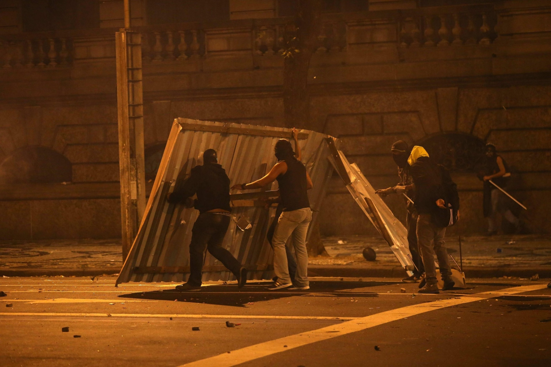 15.out.2013 - Manifestantes tentam se proteger durante confronto com policiais militares após protesto de professores no centro do Rio de Janeiro na noite desta terça-feira (15)