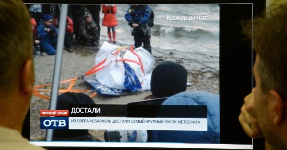 16.out.2013 - Homens olham o resgate de uma rocha de 1,5 metro de comprimento do lago Chebarkul, na Rússia, oito meses após um meteoro explodir sobre o céu de Tchelyabinsk. Se for confirmada a procedência, esse será o maior pedaço do meteorito russo já encontrado desde fevereiro