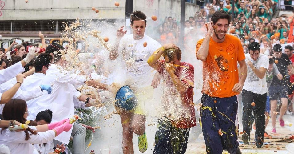 17.out.2013 - Alunos do primeiro ano de faculdade de medicina correm enquanto veteranos jogam ovos, molhos e farinha durante evento anual em honra de São Lucas, padroeiro da Universidade de Granada, em Granada, sul da Espanha