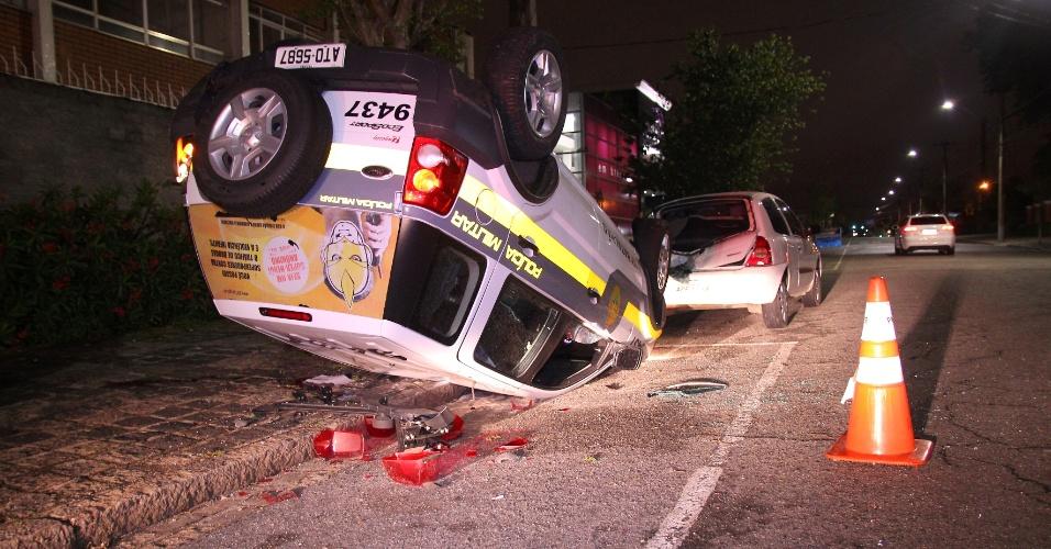 17.out.2013 - Um carro da polícia capotou após bater em um carro enquanto perseguia um suspeito e dois policiais ficaram feridos em Curitiba (PR), na madrugada desta quinta-feira (17). Os policiais perseguiam uma moto pela rua Carlos de Carvalho quando foram atingidos por um carro que seguia pela rua Francisco Rocha. Após bater, o veículo capotou e atingiu um carro estacionado. Os policiais foram encaminhados para um hospital sem risco de morte. O condutor do outro carro sofreu ferimentos leves