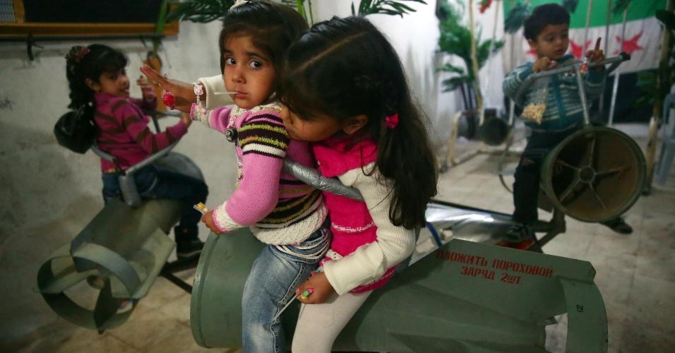 17.out.2013 - Crianças montam em balanços improvisados a partir de restos de bombas russas em um porão no bairro Duma em Damasco, na Síria. O sírio Abou Ali al-Bitar tem usado restos de armas, incluindo foguetes e morteiros, para criar objetos decorativos, instrumentos musicais e brinquedos para entreter as crianças durante o feriado muçulmano Eid al-Adha