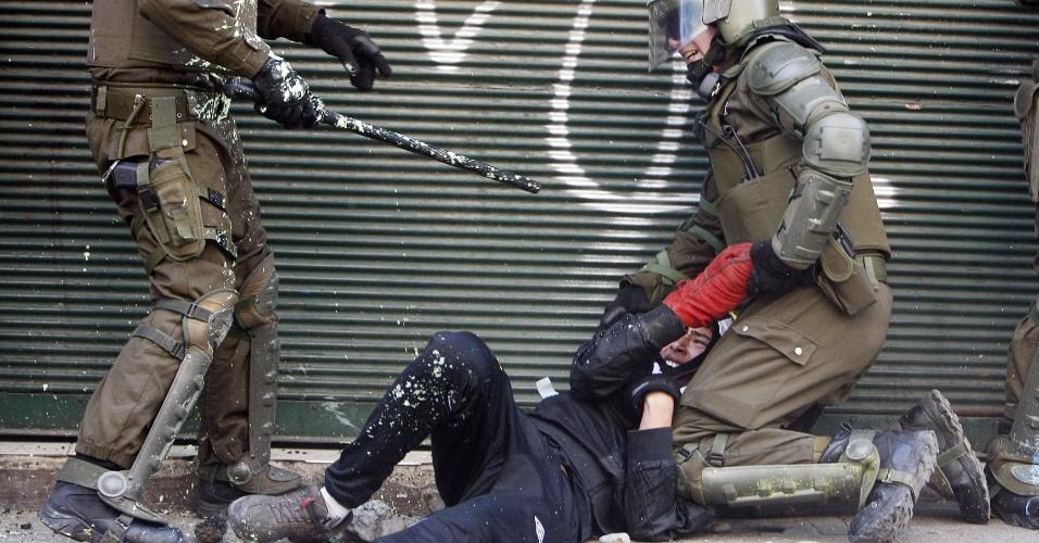 17.out.2013 - Estudante é detido por policiais durante protesto por melhorias no sistema público de educação chileno, em Santiago, nesta quinta-feira (17)