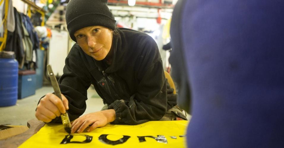 17.out.2013 - Imagem de arquivo mostra Ana Paula Maciel pintando cartaz de campanha da Greenpeace sobre o Ártico a bordo do barco