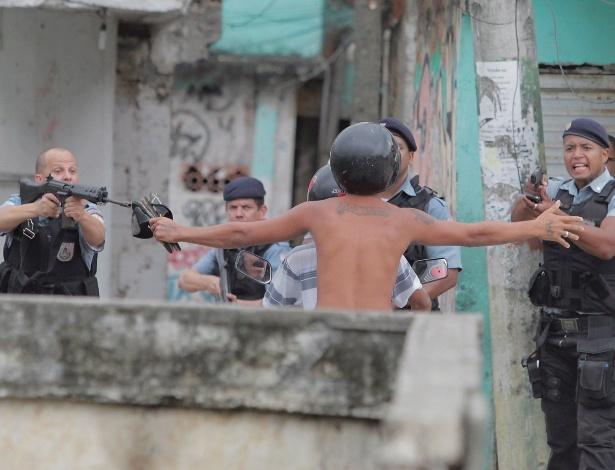 Policiais apontam armas para morador da comunidade de Manguinhos, na zona norte do Rio de Janeiro, durante protesto contra policiais militares da UPP (Unidade de Polícia Pacificadora), acusados de matarem um rapaz de 18 anos - Bruno Gonzalez/Agência O Globo