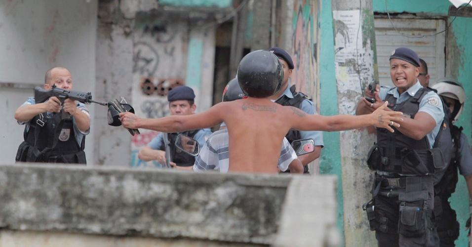 17.out.2013 - Policiais apontam armas para morador da comunidade de Manguinhos, na zona norte do Rio de Janeiro, durante protesto contra policiais militares da UPP (Unidade de Polícia Pacificadora), acusados de matarem um rapaz de 18 anos na madrugada desta quinta-feira (17). Segundo a Polícia Civil, o corpo de Paulo Roberto Pinho de Menezes foi encaminhado ao IML (Instituto Médico Legal) e passou por exame de necropsia, que poderá apontar as causas da morte, ainda desconhecidas