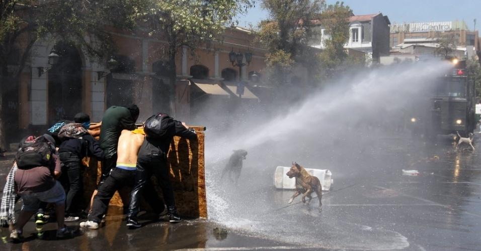 17.out.2013 - Um grupo de jovens enfrenta policiais durante protesto convocado pela Federação de Estudantes da Universidade do Chile, nesta quinta-feira (17), no centro de Santiago. Eles reivindicam educação gratuita e de qualidade