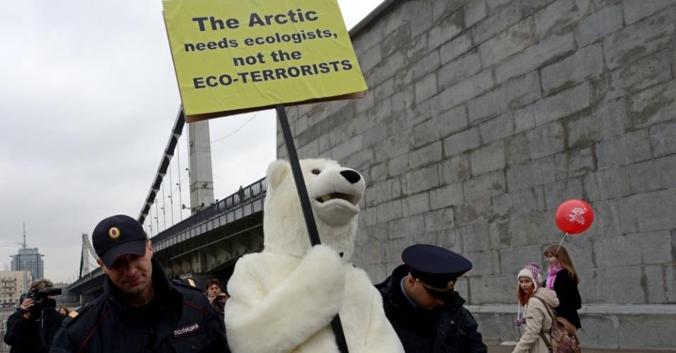 18.out.2013 - Policiais russos detêm um homem fantasiado de urso polar após conflito com ativistas do Greenpeace em Moscou. A ONG organizou em várias cidades europeias um ato de apoio aos