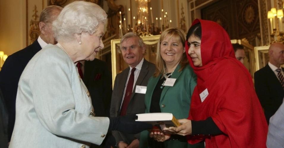 18.out.2013 - A pacifista Malala Yousafzai (à direita), jovem paquistanesa que sobreviveu a um ataque do Taleban, em 2012, entrega o livro com sua história para a Rainha Elizabeth 2ª durante uma recepção no palácio de Buckingham, em Londres (Reino Unido), nesta sexta-feira