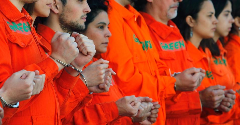 18.out.2013 - Ativistas do Greenpeace se acorrentam em frente a um posto de gasolina da Shell em Buenos Aires, na Argentina, em ato de apoio aos