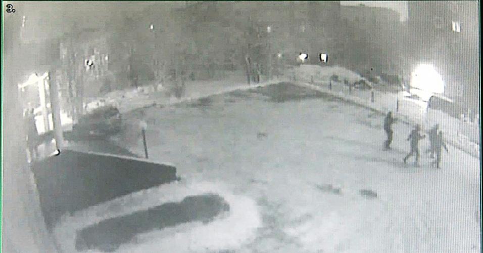 18.out.2013 - Foto capturada de vídeo de segurança do prédio do Greenpeace em Murmansk, na Rússia, na madrugada desta sexta-feira. É possível ver três homens mascarados se aproximando do local, que foi invadido e teve uma jaula de mentira, que seria usada em um protestos contra a prisão de ativistas, foi levada