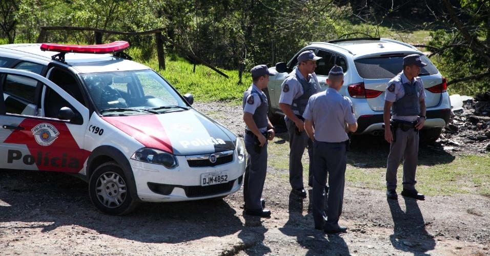 18.out.2013 - Policiais conversam perto de carro BMW onde um homem foi encontrado morto na região da Serra da Cantareira, zona norte de São Paulo. O corpo, identificado como o de um empresário sul-coreano, tem marcas de cortes no pescoço