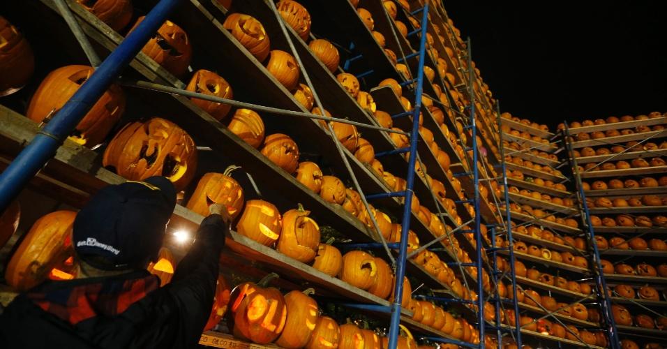 19.out.2013 - Homem acende uma abóbora esculpida entre milhares em exposição durante o Festival da Abóbora de Highwood, em Illinois, nos Estados Unidos. Os organizadores do festival estão tentando promover o maior número de abóboras iluminadas em exposição para tentar bater o recorde e entrar para o Guinness Book