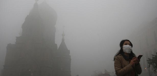 Mulher com máscara usa o celular em meio a poluição em Harbin, na China