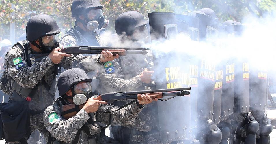 21.out.2013 Manifestantes derrubaram as grades de proteção e tentaram invadir a área interditada por causa do leilão do pré-sal, na Barra da Tijuca, no Rio; os militares reagiram com bombas de gás lacrimogêneo e balas de borracha