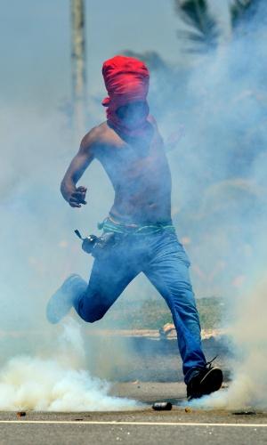 21.out.2013 Manifestantes derrubaram as grades de proteção e tentaram invadir a área interditada por causa do leilão do pré-sal, na Barra da Tijuca, no Rio; os militares revidaram com bombas de gás lacrimogêneo e balas de borracha