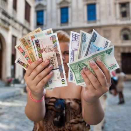 Cubana mostra pesos cubanos (cup) em uma mão e pesos conversíveis (cuc) em outra - Yamil Lage/AFP