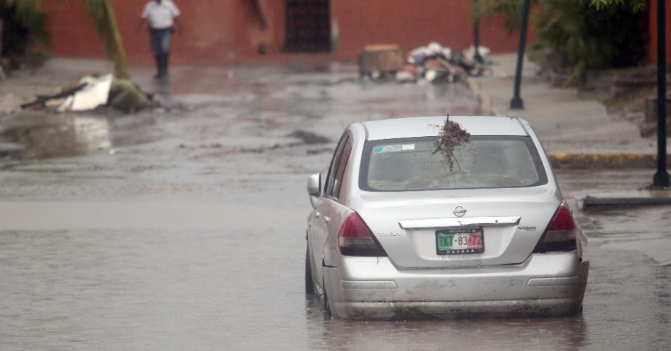 22.out.2013 - Um carro fica preso em uma rua inundada em Acapulco, no Estado mexicano de Guerrero, nesta terça-feira (22). Algumas pessoas que vivem em zonas de risco foram para abrigos, para se proteger dos possíveis ventos fortes do furacão Raymond, que se aproxima da costa mexicana