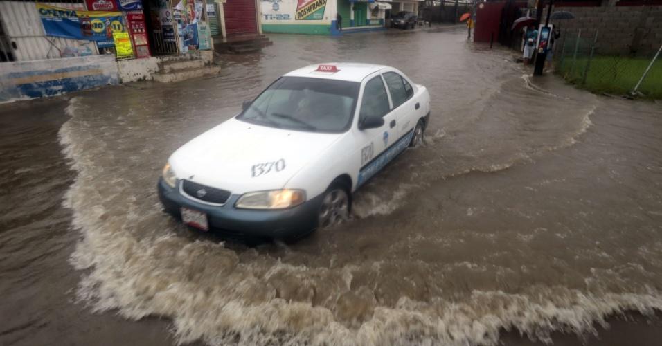 22.out.2013 - Um carro passa em uma rua inundada em Acapulco, no Estado mexicano de Guerrero, nesta terça-feira (22). Algumas pessoas que vivem em zonas de risco foram para abrigos, para se proteger dos possíveis ventos fortes do furacão Raymond, que se aproxima da costa mexicana