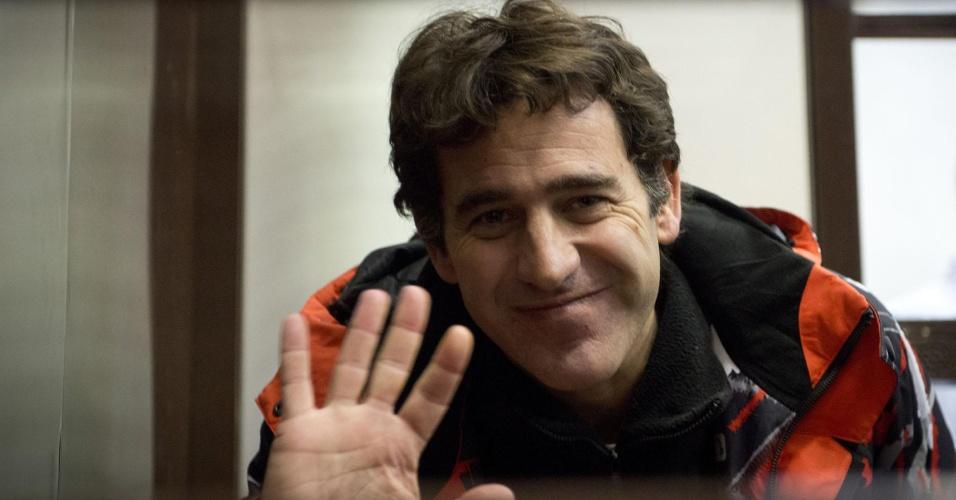 23.out.2013 - O argentino Miguel Hernan Orsi, um dos 30 ativistas do Greenpeace detidos após um protesto no Ártico, acena e sorri para jornalistas durante audiência no tribunal da cidade de Murmansk, na Rússia