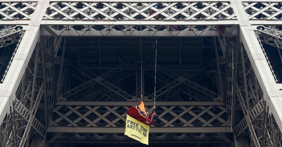 26.out.2013 - Ativistas do Greenpeace penduram cartaz na Torre Eiffel, em Paris (França), em protesto à prisão de 30 membros do grupo ambiental na Rússia no mês passado. Dentre os prisioneiros está a bióloga brasileira Ana Paula Maciel