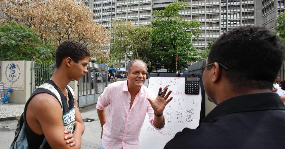 26.out.2013 - Candidatos recebem dicas de matemática com o professor Marcio Antonio Barbosa nos portões da UERJ (Universidade Estadual do Rio de Janeiro)