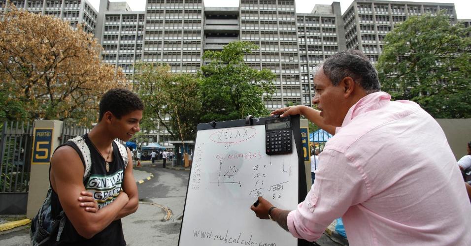 26.out.2013 - Caio Reis,17, é um dos primeiros a chegar no local de prova e recebe dicas de matemática com o professor Marcio Antonio Barbosa nos portões da UERJ (Universidade Estadual do Rio de Janeiro)