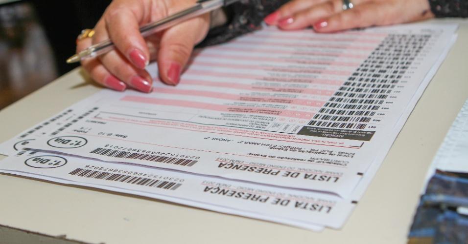 26.out.2013 - Candidato preenche lista de presença do primeiro dia de prova do Enem, na PUC, em Curitiba